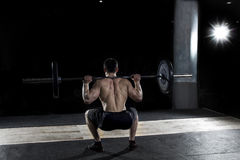 Muscular sportsman doing the squat exercise in the gym. royalty free stock photo