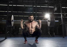 Muscular sportsman doing the squat exercise in the gym.Functiona. Muscular shirtless sportsman doing the squat exercise in the gym.Functional training stock images