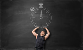 Muscular sportsman holding up big timer, drawn on the blackboard. Stock Photography