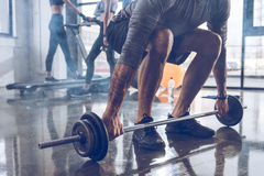 Muscular sportsman lifting barbell at gym workout. Close-up partial view of muscular sportsman lifting barbell at gym workout Royalty Free Stock Photography