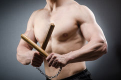 Muscular strong man with nunchucks Royalty Free Stock Image