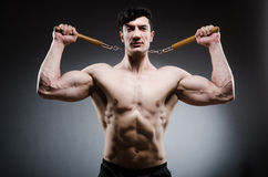 Muscular strong man with nunchucks Royalty Free Stock Images