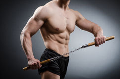Muscular strong man with nunchucks Royalty Free Stock Photo