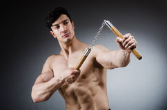 Muscular strong man with nunchucks Stock Photos