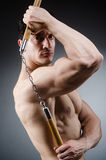 Muscular strong man with nunchucks Stock Images