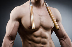 Muscular strong man with nunchucks Royalty Free Stock Photography