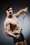 Muscular strong man with nunchucks Stock Photos
