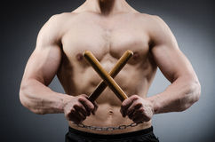 Muscular strong man with nunchucks Stock Photography