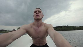 Muscular strong man row of old boat, floating on a boat with oars. Slow motion. stock video footage