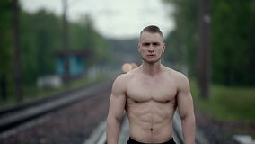 Muscular strong man stands on railroad tracks. Medium shot stock video