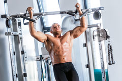 Muscular strong man working out at a gym. Stock Photography