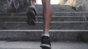 Muscular strong tanned male legs run up stairs. Close up back view of sportive powerful male legs. Slim athletic man runs up stair