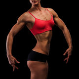 Muscular strong woman. On a black background royalty free stock photo