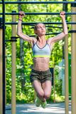 Muscular strong woman on the crossbar is engaged in the park. Press exercises stock photos