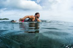 Muscular surfer paddling in the ocean. Muscular surfer with beard paddling in the ocean Royalty Free Stock Photography