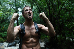 Muscular survivor man in jungle rainforest. Cheering aggressive. Strong male survival concept with guy celebrating cheerful in forest at night showing muscles Stock Image
