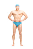 Muscular swimmer with a swim cap and goggles. Full length portrait of a young muscular swimmer with a blue swim cap and black goggles isolated on white Stock Photography