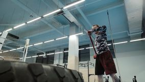 Muscular tattooed man with hammer hits the huge wheel in the gym in slow motion. Muscular strong man with tattoo on his foot with a hammer hits the huge wheel in stock footage