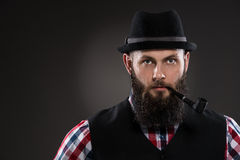 Muscular tattooed man holding a pipe in his mouth Royalty Free Stock Photos