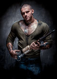 Muscular tattooed man with jackhammer Stock Photos