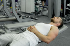 Muscular tired man lies on a bench after exercise in the gym Stock Images