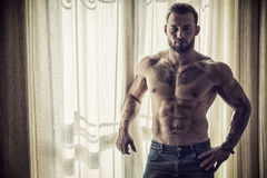 Muscular topless man standing by window Stock Photo
