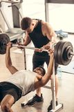 Muscular trainer helping sportsman lifting barbell with heavy weights. In gym royalty free stock images