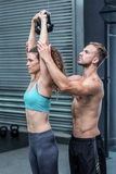 Muscular trainer show how to lift kettlebells. Attentive muscular trainer showing how to lift kettlebells Stock Photos