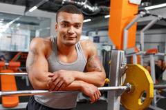 Muscular weightlifter leaning on barbell in gym Stock Photography