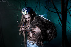 Muscular werewolf with dreadlocks with long nails among the bran royalty free stock image