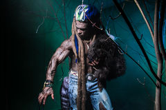 Muscular werewolf with dreadlocks with long nails among the bran stock photography
