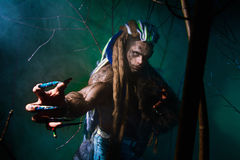 Muscular werewolf with dreadlocks with long nails among the bran Royalty Free Stock Images