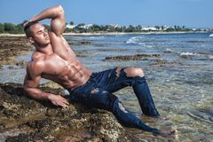Muscular wet naked guy lying on the beach with a naked torso stock photography