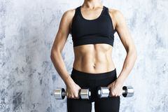 Muscular woman with barbells on textured wall. royalty free stock photo