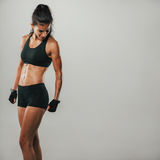 Muscular woman in black sports shorts and top Stock Photos