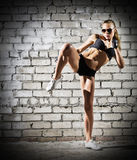 Muscular woman on brick wall (dark version) Royalty Free Stock Images
