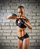 Muscular woman on brick wall (normal version) Royalty Free Stock Images