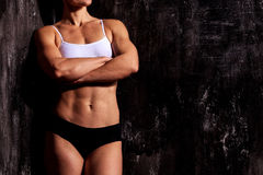 Muscular woman on a dark background Royalty Free Stock Image