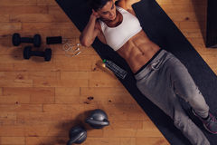 Muscular woman doing abs workout in gym Stock Photos