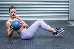 A muscular woman doing core exercises. Muscular woman doing core exercises with a medecine ball royalty free stock images