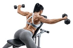 Muscular woman doing exercise with dumbbells for muscles of back. stock image