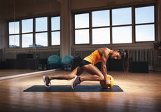 Muscular woman doing intense core workout. Muscular woman in gym working out on her core body. Strong woman exercising with kettlebell in sports club Royalty Free Stock Photo