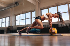 Muscular woman doing intense core workout. Portrait of a fit and muscular woman doing intense core workout with kettlebell in gym. Female exercising at crossfit stock photo