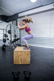 Muscular woman doing jumping squats Stock Photo
