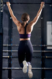 Muscular Woman Doing Pull Ups in Crossfit Gym Stock Image