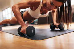 Muscular woman doing push-ups on dumbbells. In gym. Powerful female exercising in health club Stock Photos