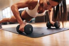 Muscular woman doing push-ups on dumbbells Stock Photos