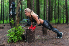 Muscular woman doing push-ups at park street work out stock photo