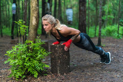 Muscular woman doing push-ups at park street work out royalty free stock photography