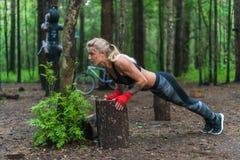 Muscular woman doing push-ups at park street work out stock photos